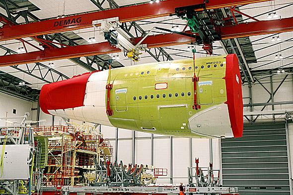 Processkran som lyfter del av flygplan